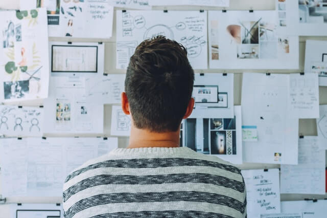 Lead Generation Vs Lead Nurturing: What's the Difference? - Man looking at wall covered in ideas and notes.